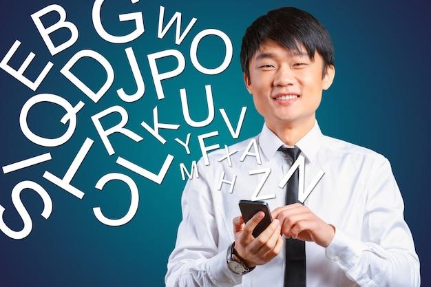 Azjatycki biznesmen opowiada na mobilnym telefonie komórkowym