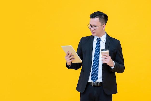 Azjatycki biznesmen patrzeje pastylka komputer podczas gdy pijący kawę