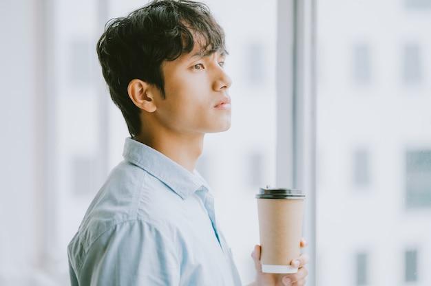 Azjatycki biznesmen pije kawę przy oknie