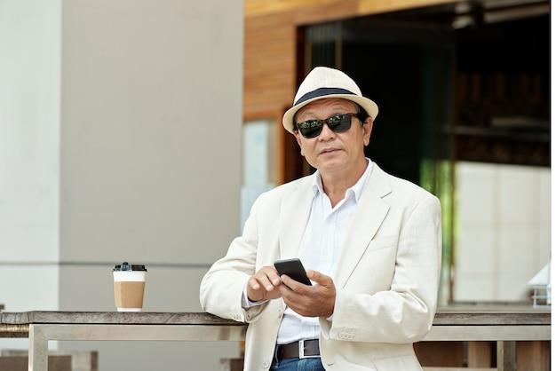 Azjatycki biznesmen pracujący w kawiarni na świeżym powietrzu