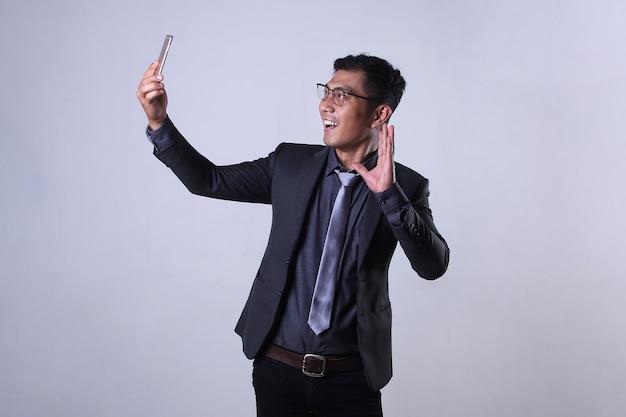 Azjatycki biznesmen przeprowadzający rozmowę wideo przez smartfona