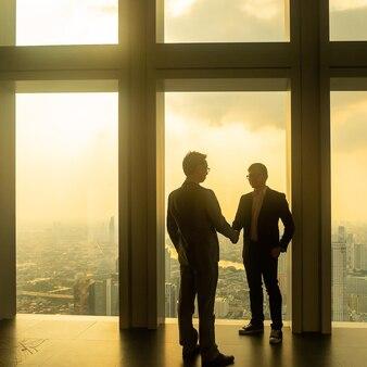 Azjatycki biznesmen ściskając ręce w biurze.