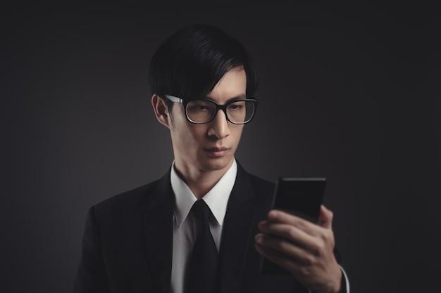 Azjatycki biznesmen skanuje twarz za pomocą inteligentnego telefonu za pomocą systemu rozpoznawania twarzy.