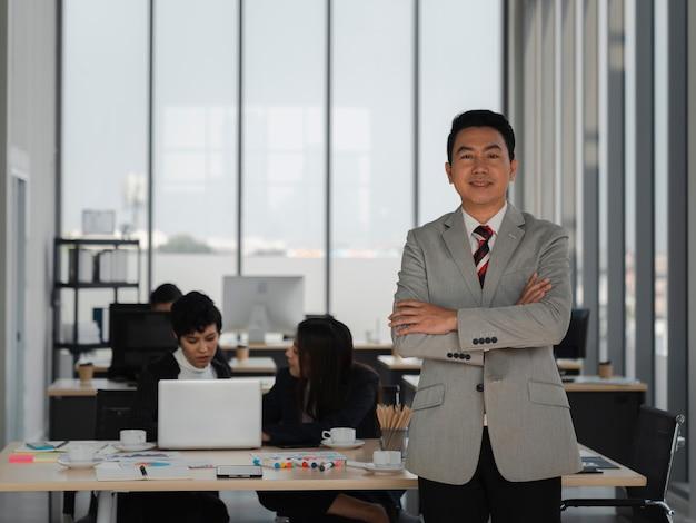 Azjatycki biznesmen skrzyżował ręce i czeka z pewnością siebie w biurze z różnorodnością pracujących ludzi, liderem zespołu biznesowego, sukcesem, analizą i koncepcją strategii