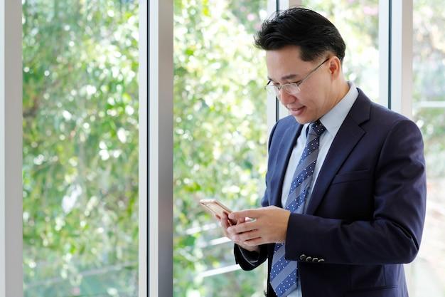 Azjatycki biznesmen trzyma mądrze telefon z szczęśliwą uśmiechniętą twarzy pozycją okno
