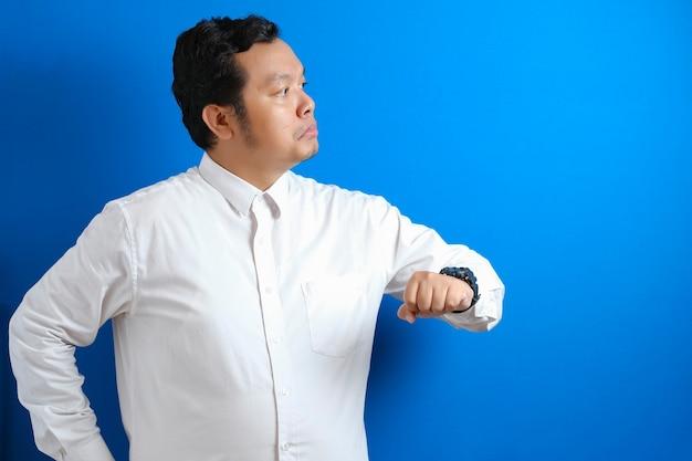Azjatycki biznesmen ubrany w białą koszulę, sprawdzający czas na zegarku, zmęczony, zirytowany gestem za zbyt długie czekanie