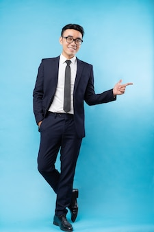 Azjatycki biznesmen ubrany w garnitur stojąc i wskazując na niebieskiej ścianie