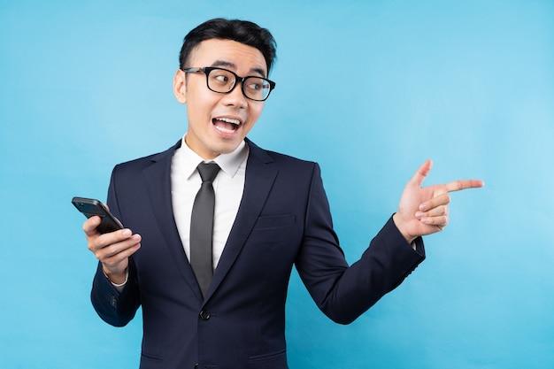 Azjatycki biznesmen ubrany w garnitur, trzymając smartfon na niebieskiej ścianie