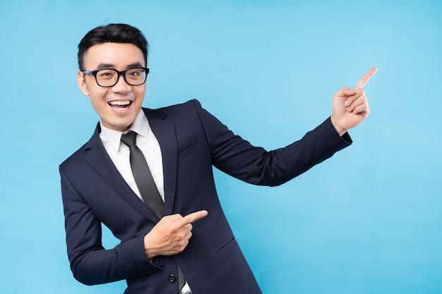 Azjatycki biznesmen ubrany w garnitur, wskazując na niebieskiej ścianie