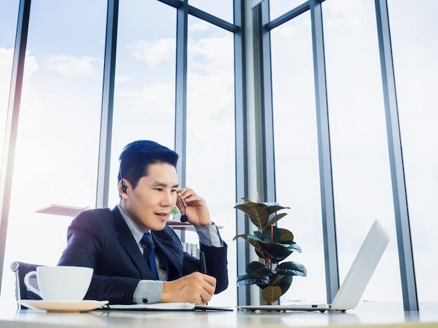 Azjatycki biznesmen ubrany w garnitur z zestawem słuchawkowym robienia notatek i korzystania z laptopa na biurku w biurze w pobliżu ogromnego szklanego okna i nieba