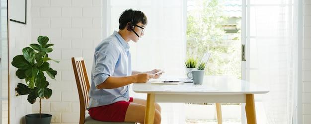 Azjatycki biznesmen ubrany w koszulę i szorty podczas pracy w domu w salonie rozmawia ze współpracownikami w trakcie rozmowy wideo. samoizolacja, dystans społeczny, kwarantanna w celu zapobiegania koronawirusom.