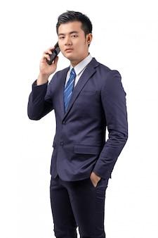 Azjatycki biznesmen używa smartphone z odosobnionym na białym tle.