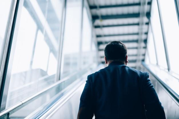 Azjatycki biznesmen w garniturze i jazda na schodach ruchomych na stacji metra podczas jego porannej dojazdy do pracy