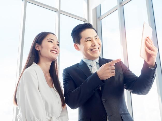 Azjatycki biznesmen w garniturze i młoda kobieta nawiązywanie połączenia wideo z cyfrowego tabletu na szklanym oknie