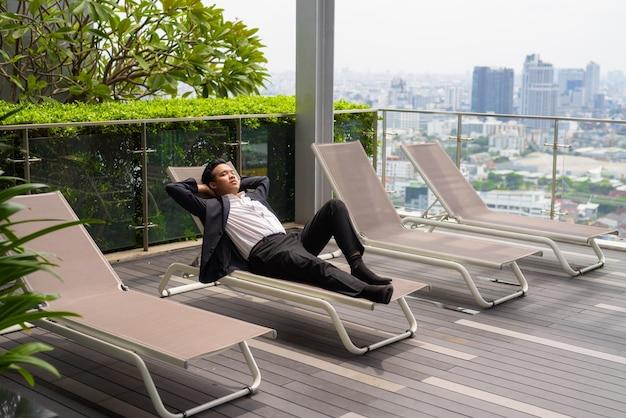 Azjatycki biznesmen w garniturze i relaksujący się na świeżym powietrzu, leżąc na leżaku w mieście
