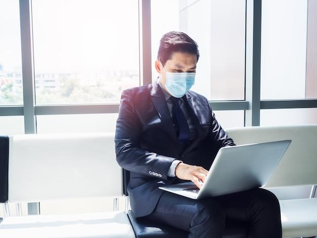 Azjatycki biznesmen w garniturze na sobie ochronną maskę na twarz za pomocą laptopa na kolanach, siedząc w nowoczesnym biurowcu w pobliżu ogromnego szklanego okna
