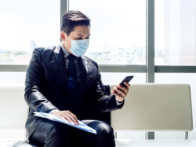 Azjatycki biznesmen w garniturze noszenie maski ochronnej przy użyciu telefonu komórkowego, siedząc w nowoczesnym budynku biurowym w pobliżu ogromnego szklanego okna.