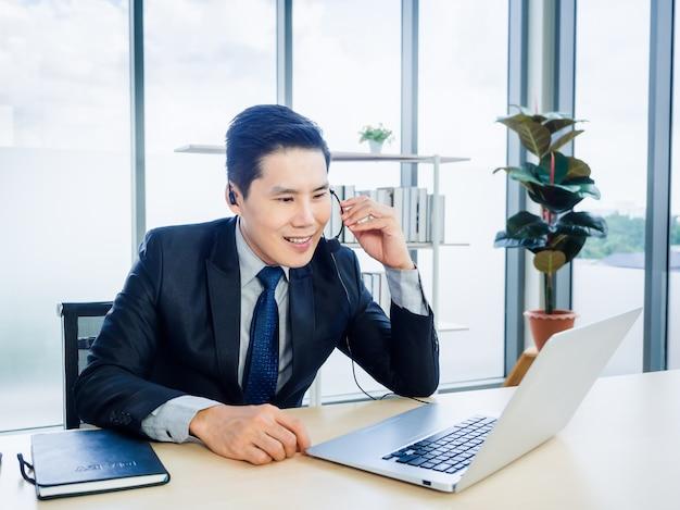 Azjatycki biznesmen w garniturze z zestawem słuchawkowym za pomocą laptopa na biurku w biurze. mężczyzna w słuchawkach, mikrofon patrząc na ekranie komputera z połączeniem konferencyjnym