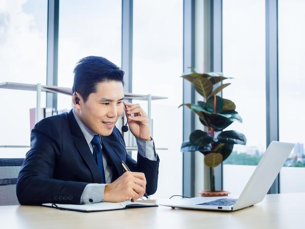 Azjatycki biznesmen w garniturze z zestawem słuchawkowym za pomocą laptopa na biurku w biurze. mężczyzna w słuchawkach z mikrofonem, robienie notatek i korzystanie z laptopa z połączeniem konferencyjnym