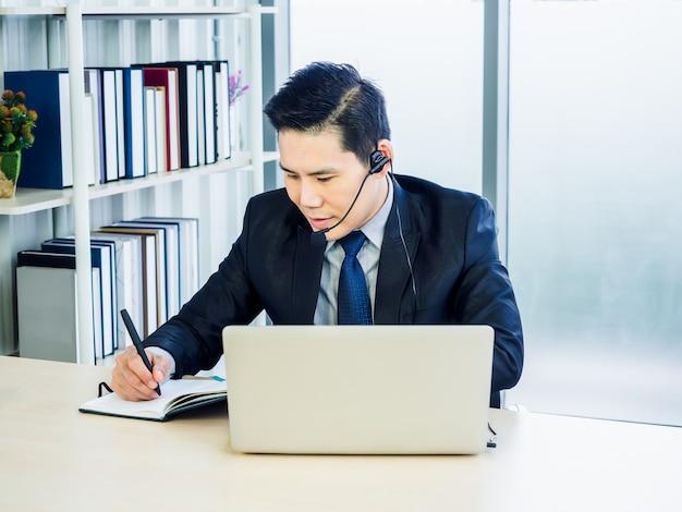 Azjatycki biznesmen w garniturze z zestawem słuchawkowym za pomocą laptopa na biurku w biurze
