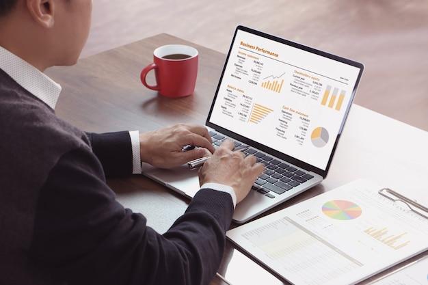 Azjatycki biznesmen w swobodnym stroju przy użyciu laptopa podczas przeglądania sprawozdań finansowych pod kątem zwrotu z inwestycji, roi i wyników biznesowych.