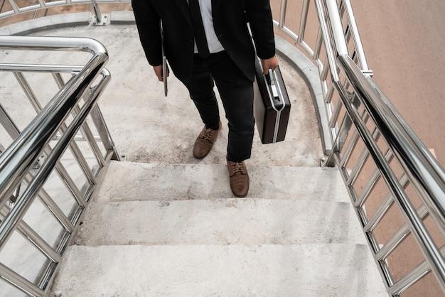 Azjatycki biznesmen wchodzi po schodach i niesie ze sobą laptopa i torbę, aby ubiegać się o pracę.
