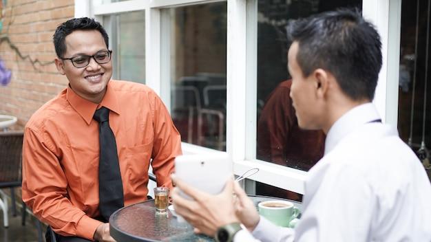 Azjatycki biznesmen wskazując tabletkę jej przyjaciel