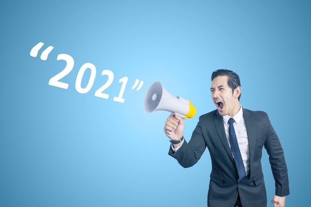 Azjatycki biznesmen z megafonem ogłasza rok 2021. szczęśliwego nowego roku 2021