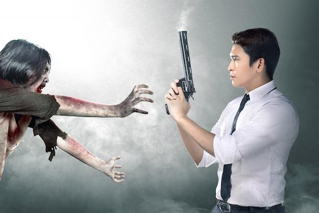 Azjatycki biznesmen z pistoletem na ręce stawia czoło zombie