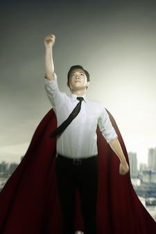Azjatycki biznesmen z płaszczem latającym jak superbohater