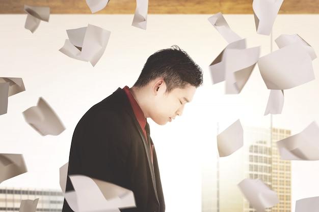 Azjatycki biznesmena uczucie deprymujący z latającymi papierami pracy
