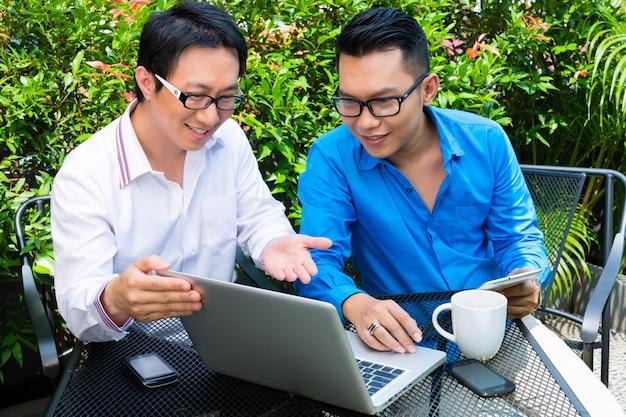 Azjatycki biznesmenów pracować plenerowy