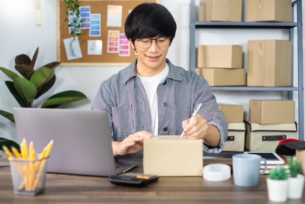 Azjatycki biznesowego początkującego przedsiębiorcy mśp przedsiębiorca lub freelance pracujący w kartonie przygotowuje pudełko dla klienta, sprzedaż online, handel elektroniczny, pakowanie i wysyłkę.