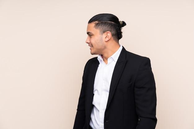 Azjatycki biznesowy mężczyzna odizolowywający na beż ścianie patrzeje strona