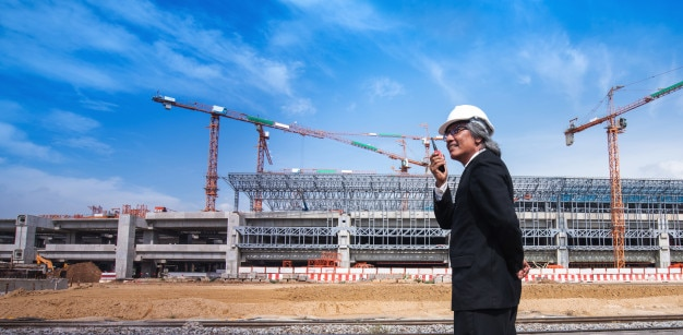 Azjatycki biznesowy mężczyzna z walky talky na budowie i basztowych żurawiach w tle