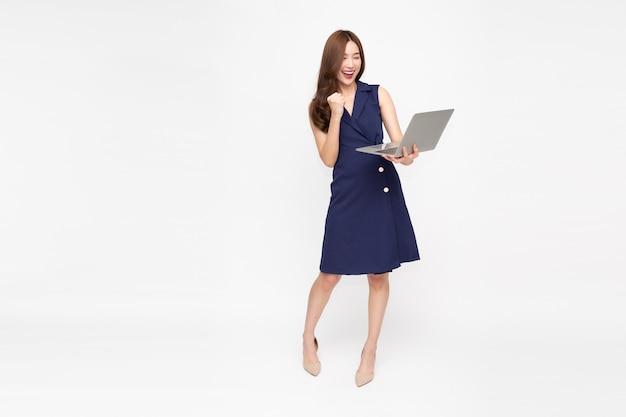 Azjatycki bizneswoman gospodarstwa laptopa na białym tle na białej ścianie