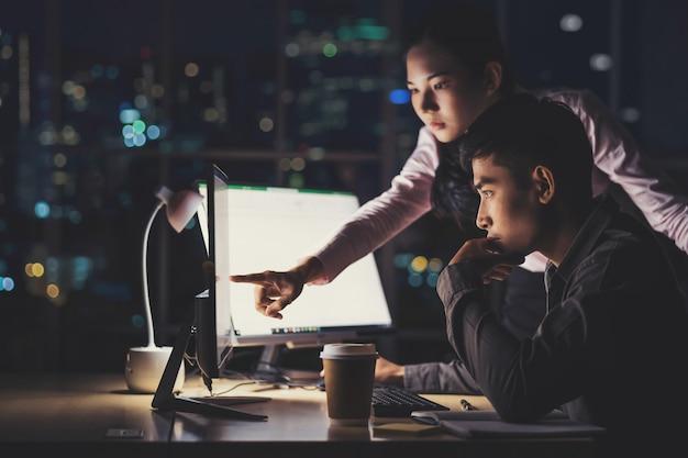 Azjatycki bizneswoman i biznesmen pracuje mocno póżno wraz z technologia komputerem w biurze