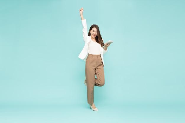 Azjatycki bizneswoman stojący i trzymający się za ręce kalkulator na białym tle na zielonym tle