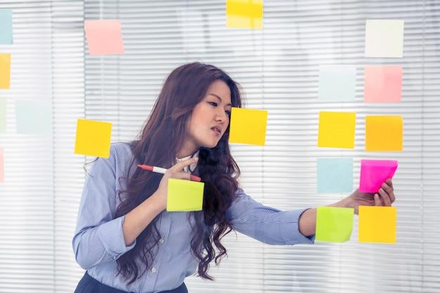 Azjatycki bizneswoman używa kleiste notatki na ścianie w biurze
