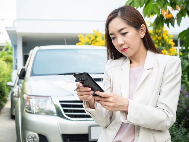 Azjatycki bizneswoman używa mądrze telefon przeciw samochodowi.