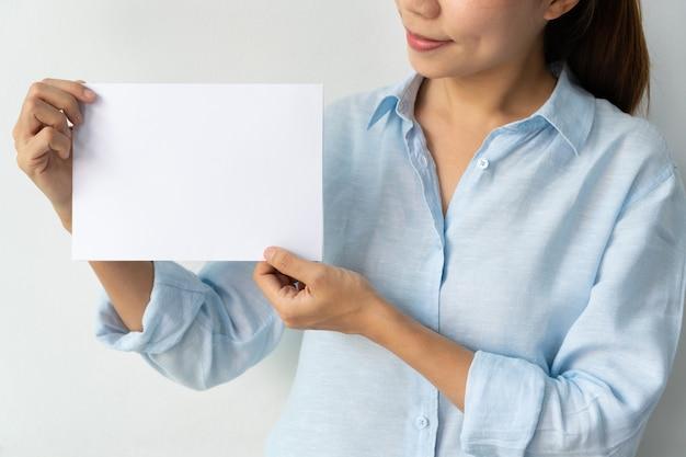 Azjatycki bizneswoman w niebieskiej koszuli trzyma pusty arkusz papieru w rękach izolowanych na białym