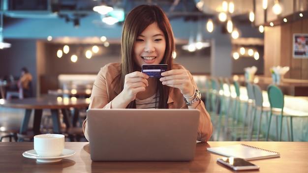 Azjatycki bizneswoman w przypadkowym kostiumu używać kredytową kartę z komputerem dla online zakupy