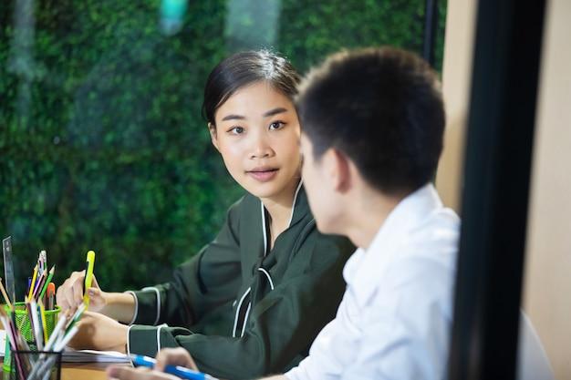 Azjatycki bizneswoman wyjaśnia coś jego kolega