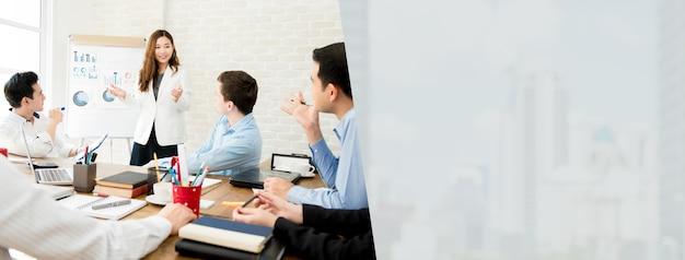 Azjatycki bizneswomanu lider przedstawia pracę w spotkaniu z jej kolegami, sztandaru tło