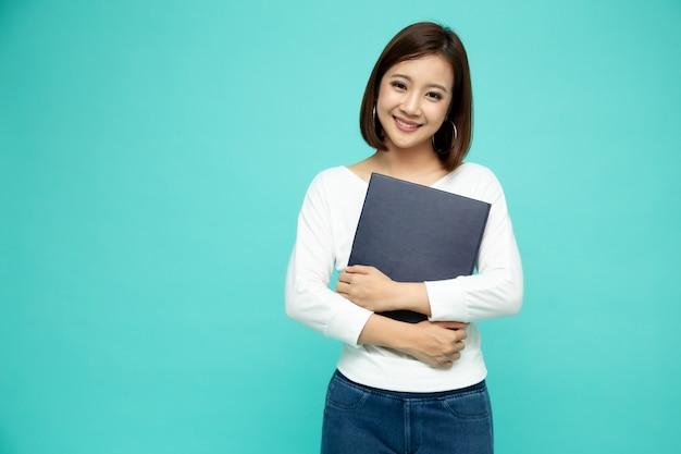 Azjatycki bizneswomanu mienia dokumentów kartoteki stoi nad zieleni ścianą