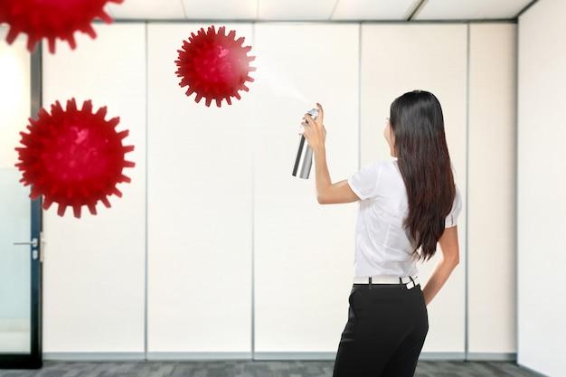 Azjatycki bizneswomanu opryskiwania środek dezynfekujący w biurowym pokoju