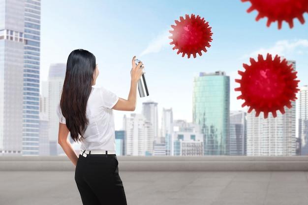 Azjatycki bizneswomanu opryskiwania środek dezynfekujący w budynku biurowym