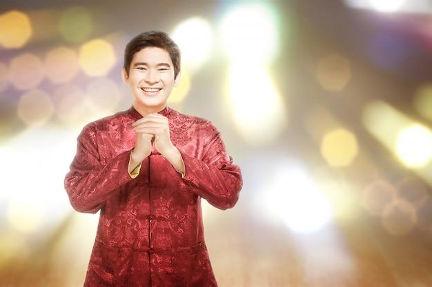 Azjatycki chińczyk w sukience cheongsam z gestem gratulacyjnym