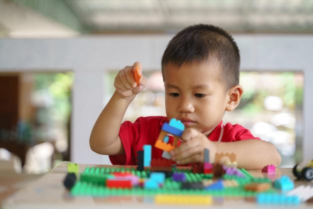 Azjatycki chłopiec bawi się klocki