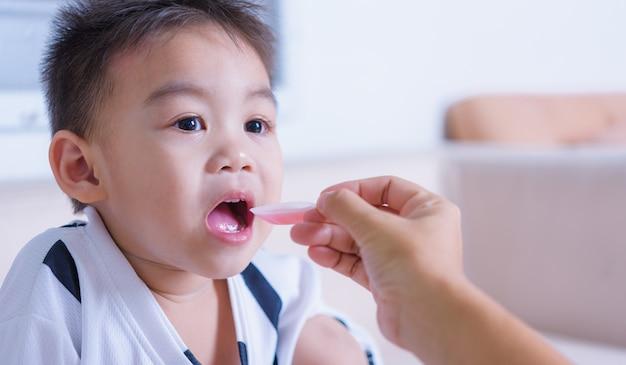 Azjatycki chłopiec bierze lek łyżką